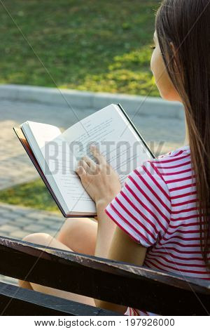 Beautiful girl relaxes and reads a book on the bench in the park. A woman keeps a finger on the text during reading. Back view