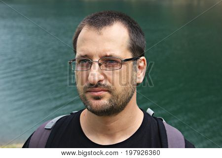 Portrait of a man with lake in the background