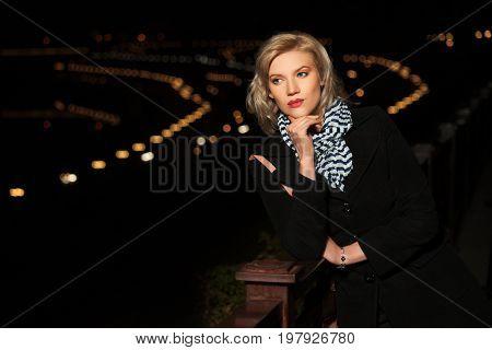 Happy fashion blond woman in a night city street. Stylish female model in black coat outdoor