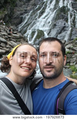 Portrait of a happy couple taking selfie in the mountains, near waterfall.