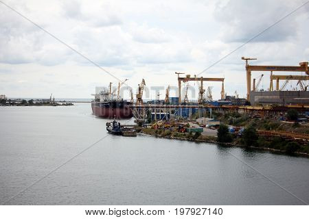Heavy cranes in the port loading big cargo ship