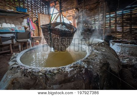 Boiling rock salt , Lapping crystallized salt from boiled salt water to dried up the basket. Nan ,Thailand. HDR.Image has grain or blurry or noise when view at full resolution.