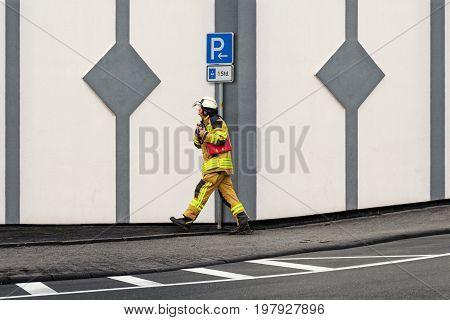Feuerwehrmann entlang eines Hauses auf dem Weg zum Einsatzort