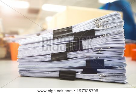 Pile of unfinished documents on office desk, Stack of business paper with black clips.