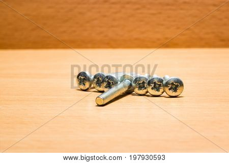 A bunch of screws for fastening on a wooden background are small auxiliary tools for fastening out of durable material