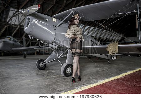 Bomber, Beautiful redhead girl dressed in style pinup of the second world war, next to a military plane