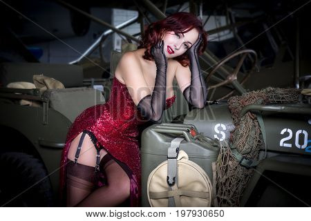 Retro Beautiful redhead girl dressed in style pinup of the second world war, next to a military jeep
