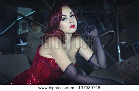 40s Beautiful redhead girl dressed in style pinup of the second world war, next to a military jeep