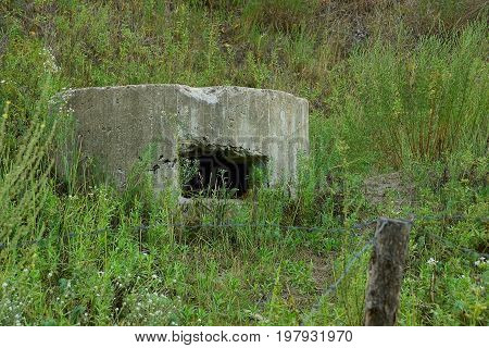 The old embrasure of the military pillbox in the grass behind the barbed wire