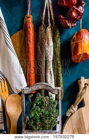 Assortment of traditional Spanish charcuterie meat sausages fresh herbs thyme kitchen utensils towel wood cutting board rustic interior