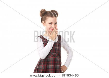 Portrait of naughty little girl in school uniform against white background