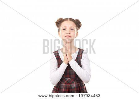 Portrait of cute girl in school uniform pleading against white background