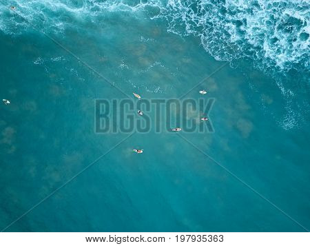 Surfers swim in blue water aerial above view. Top view on surfer in blue water wait for wave