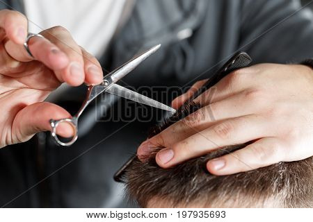 men's haircut with scissors at salon. Barber cuts the hair of the client with clipper at barbershop. Men's hairstyling and haircutting in a barber shop or hair salon.