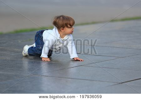 Little girl crawls on marble slabs outdoors in summer