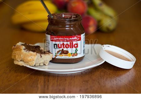 July 18th, 2017, Cork, Ireland - Nutella jar and a slice of homemade break with healthy fruits in the background