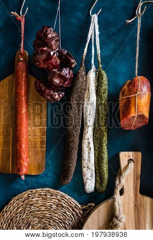 Variety of traditional Spanish charcuterie meat sausages towel wood cutting board rustic kitchen interior
