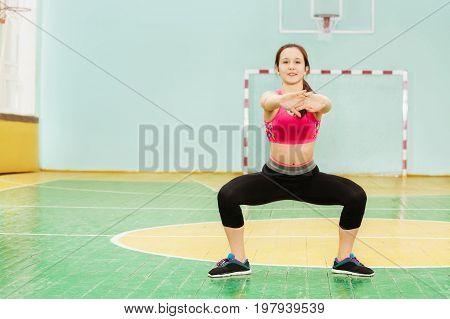 Portrait of beautiful teenage girl performing sumo squat, exercising in gym