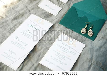 Wedding invitation cards emerald envelope and menu with bridal earrings on crumpled light green fabric