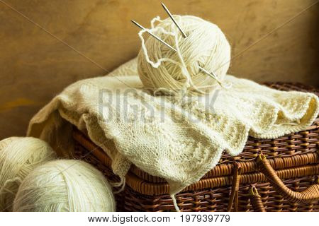 Handmade knitwear clew of white wool yarn on vintage hobby and crafts wicker chest wool clews wood table cozy atmosphere shabby chic style