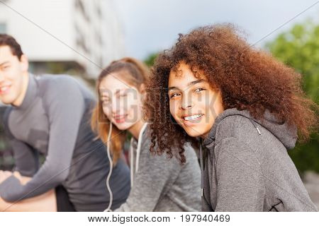 Close-up portrait of smiling African sportswoman exercising outdoors with friends
