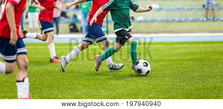 Soccer Player Action On Stadium. Youth Football Tournament Game. Young Boys Running and Kicking Soccer Ball on Green Soccer Pitch.