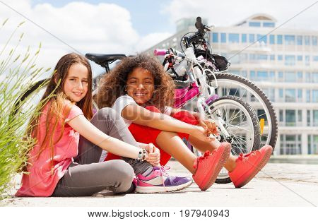 Portrait of two happy preteen girls sitting on the road next to their bicycles, resting after cycling in summer city