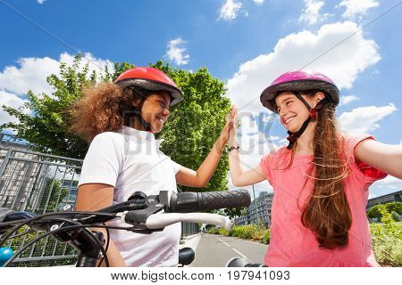 Portrait of two happy bike riders, Caucasian and African preteen girls, giving high five after racing at city park