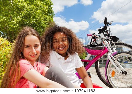 Close-up portrait of two preteen girls resting after cycling in summer city, smiling and looking at camera