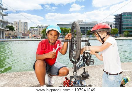 Portrait of African preteen boy repairing bicycle wheel with spanner, while his friend inflating tires using air pump outdoors on river embankment