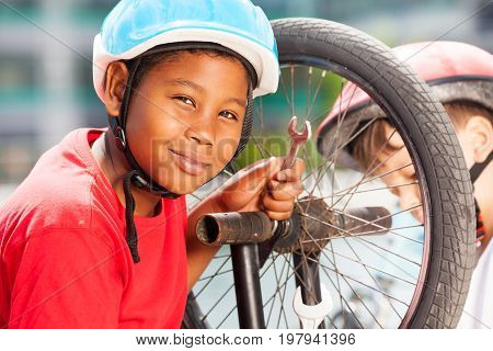 Close-up portrait of African 10-12 years old boy in safety helmet using a spanner while repairing his bicycle wheel