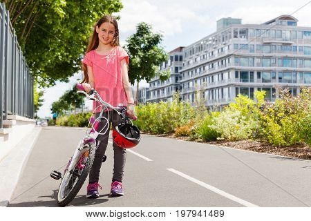 Portrait of happy preteen girl standing with bike on cycle path at city park in summer