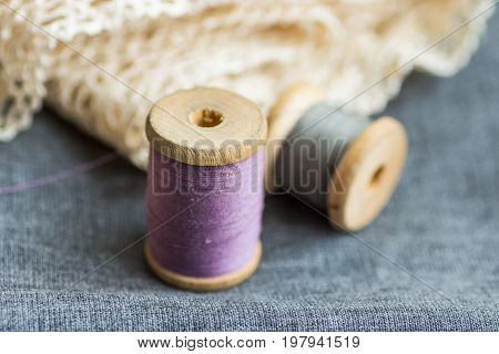 Vintage wood spools with lilac and grey threads on folded wool fabric cotton off-white lace hobby swing concept copyspace header for website