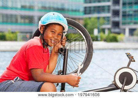 Smiling African 10-12 years old boy in safety helmet using a spanner while repairing his bicycle outdoors in summer