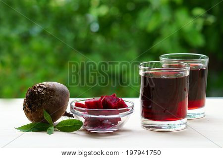 Two glasses of beet juice next to a bowl of beet, diced