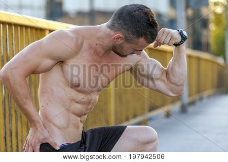 Young Muscular Young Man  Doing Exerciseson The Bridge