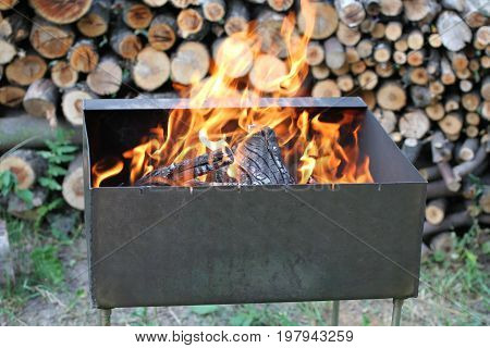 Burning fire woods in brazier against fire wood stack background