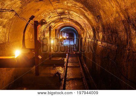 Round underground technical tunnel with a narrow-gauge railway