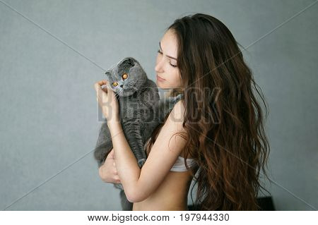 Sexy beautiful brunette girl in underclothes with cute cat resting at home studio
