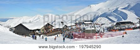 Mount Hutt New Zealand - July 30 2017: Panoramic view of the Mount Hutt Ski Field at Lunch Time. Skiers prepare to ride on the Chairlift outside the restaurant Canterbury New Zealand.
