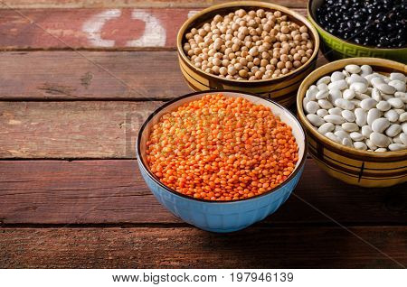 Assorted beans in bowls with red lentil, chick-pea and kidney bean on wooden background. Horizontal, copy space