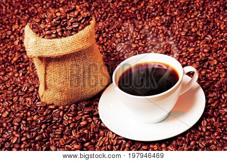 coffee beans with burlap bag and steaming coffee cup