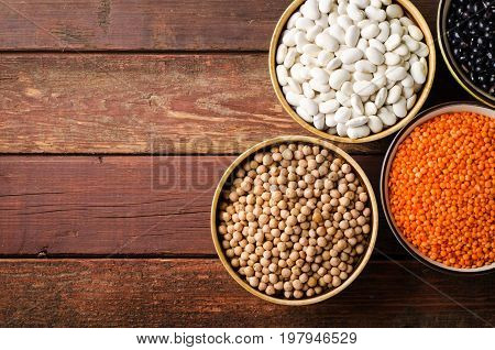 Assorted beans in bowls with red lentil, chick-pea and kidney bean on wooden background. Horizontal top view, copy space