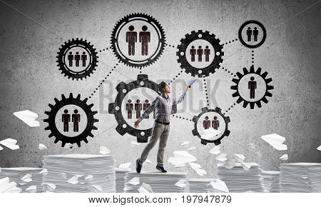 Man in casual wear keeping hand with book up while standing among flying paper planes with social gear structure on background. Mixed media.