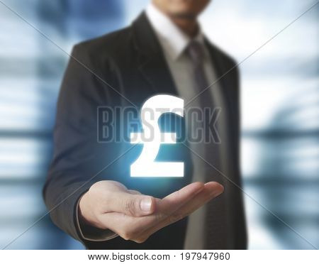 Businessman with pound sterling currency symbol coming from hand on blue digital light background, financial concept