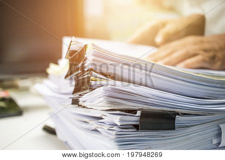 Businessman hands searching data information in Stack of papers files on work desk in office business report paper or piles of unfinished documents achives with clips on offices indoor Business concept