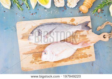 fresh sea fish preparation - top view of two dorada fish on cutting board