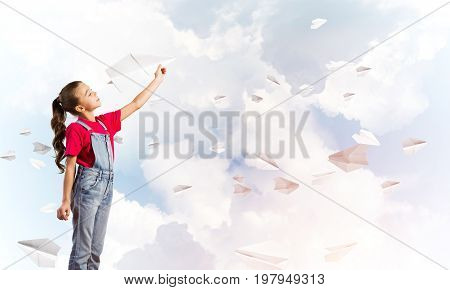 Little cute girl against sky background playing with paper airplane