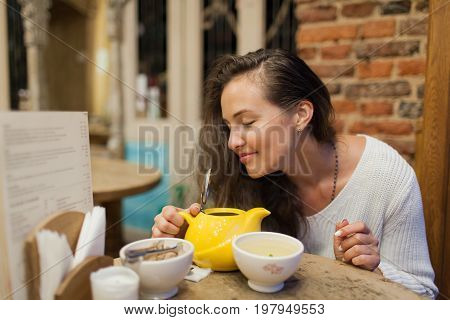The Pretty Young Girl Inhales The Aroma Of Freshly Brewed Tea Sitting In A Cafe