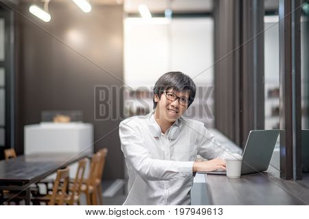Young Asian business man dressed in casual style working in coffee shop with laptop computer. Digital nomad and IT freelance lifestyles work life balance concept